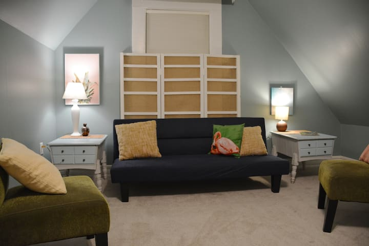 The Palm Room, our upstairs den. You'll find puzzles, games, books, and decks of cards. The futon can accommodate 1-2 guests.