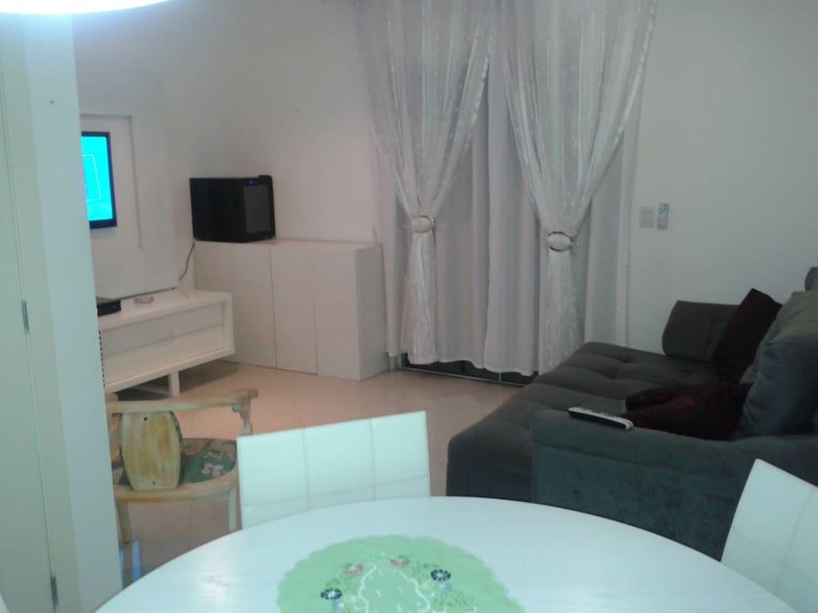 Sala com mesa 4 cadeiras e sofá cama