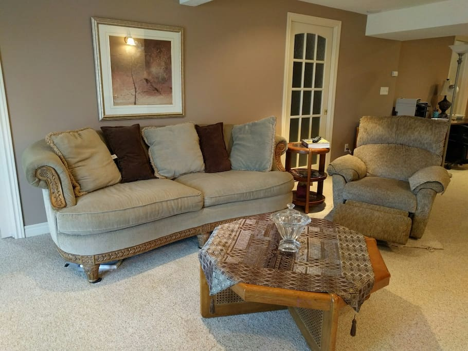 Large living room with ample seating, gas fireplace and walk out to private patio, facing large pond