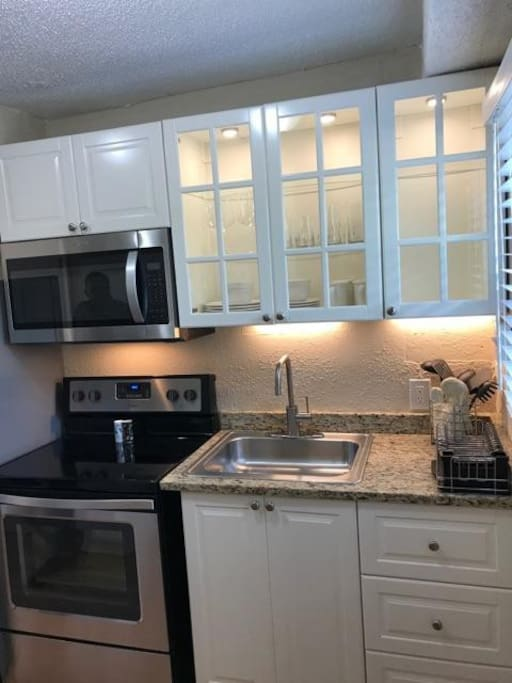 Kitchen with new appliances, fully stock with dishes, pots, pans, wine glasses, wine opener, silverware and cooking utensils.
