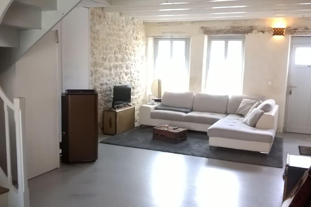 Salon cosy avec écran plat, canapé d'angle et poêle à granules sur pièce de vie de 44 m2.