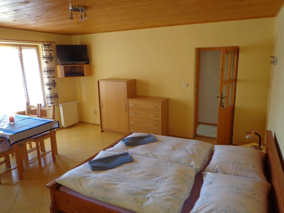 Large room with three beds and dinning table