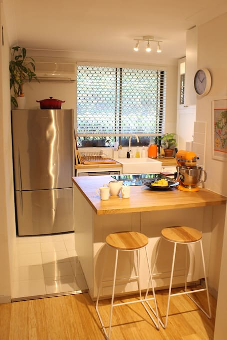 Open plan kitchen with leafy view and breakfast bar