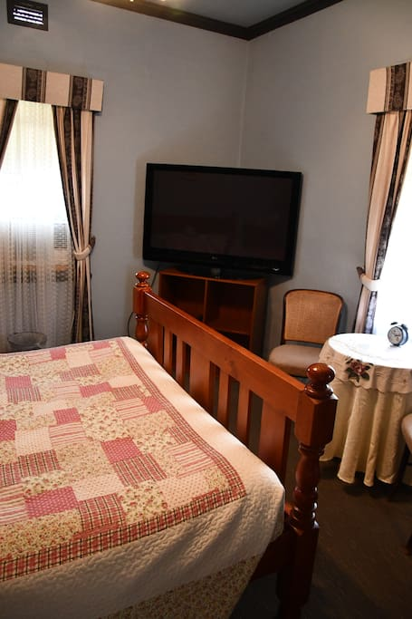 This is the largest of the 4 rooms, it's duel aspect with a 50 inch T.V., it has 2 chairs with a small table, a wardrobe, a queen bed, dressing table with tea and coffee making area. It also has a fan and an air conditioner.