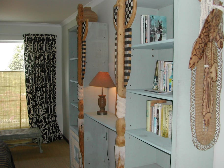 """another view of bedroom with """"African"""" custom bookshelves and cupboards"""