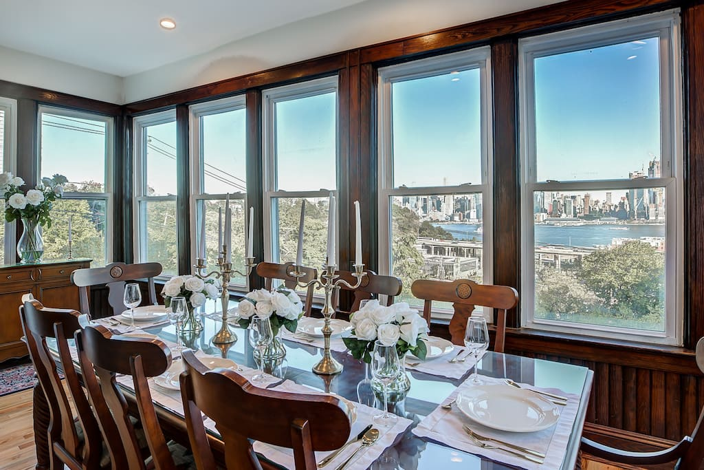 Dining room with three full walls of windows overlooking the Hudson River with a full view of the Manhattan skyline.