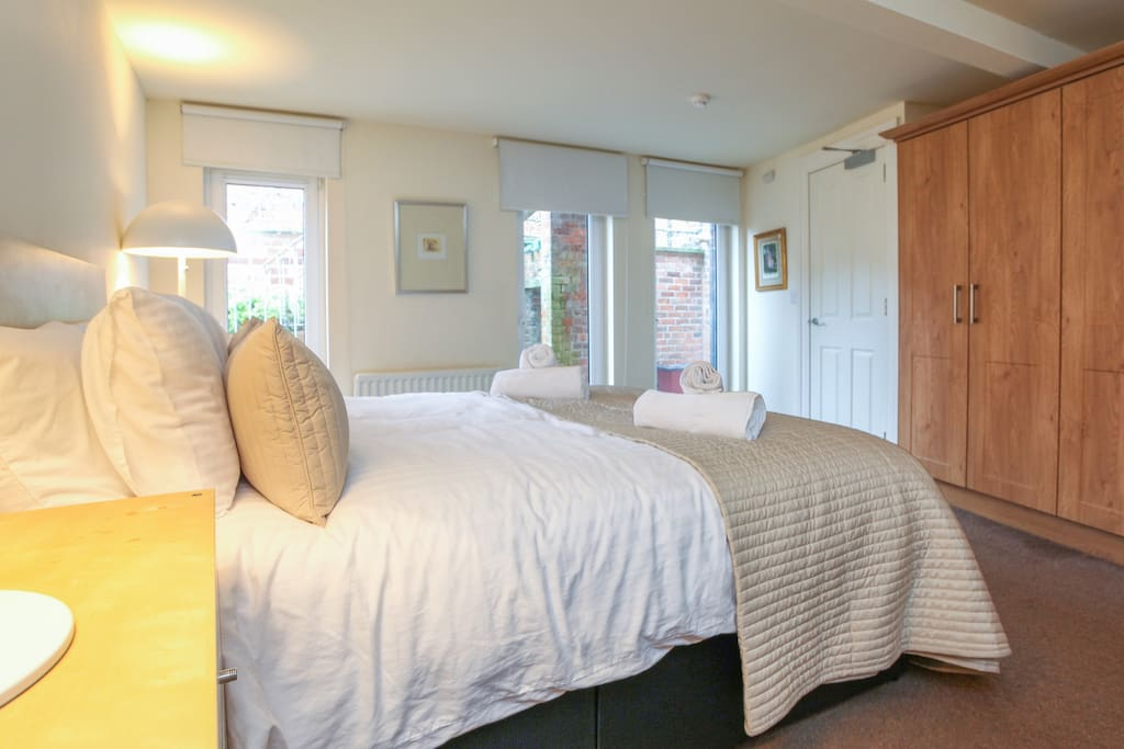 Ceiling to floor windows for maximum light with oak fitted wardrobes