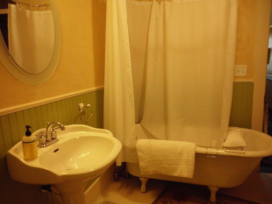 Shared spacious bath with claw foot tub.