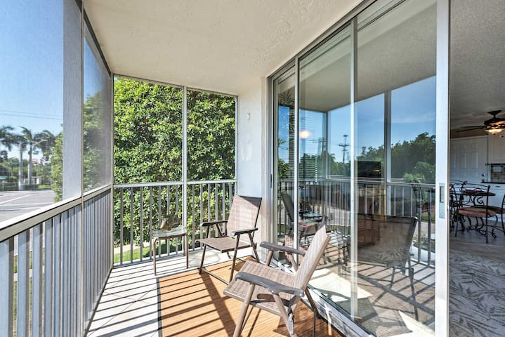 The screened-in balcony offers a great view of the estuary through lush trees.