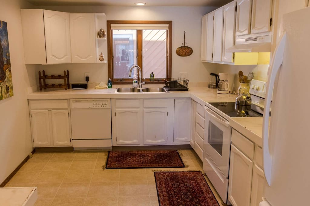 Open plan kitchen has plenty of dishware to cater to the whole family