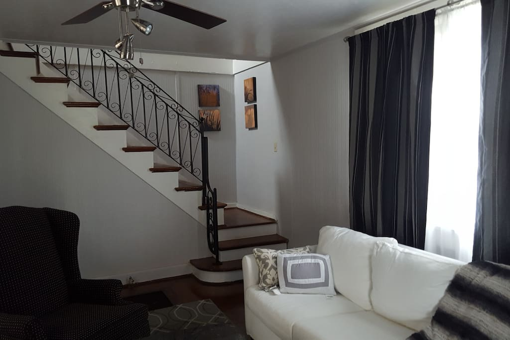 This is a view of living room leading upstairs to bedrooms and full bath. Staircase has appealing wrought iron railing.