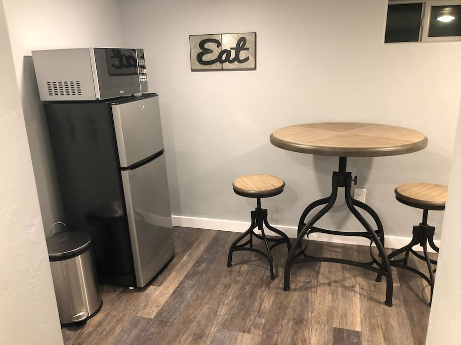 Eating and work space with mini fridge and microwave for snacks and beverages.