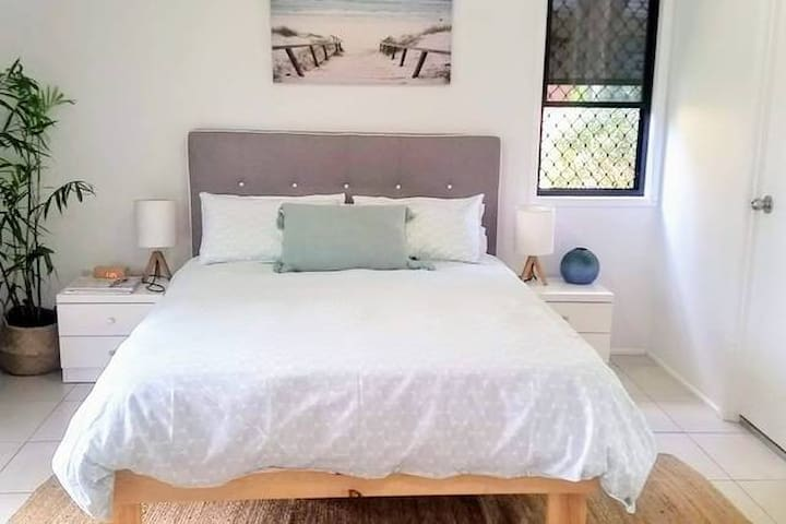 Downstairs studio bedroom with queen bed and balcony and bathroom.