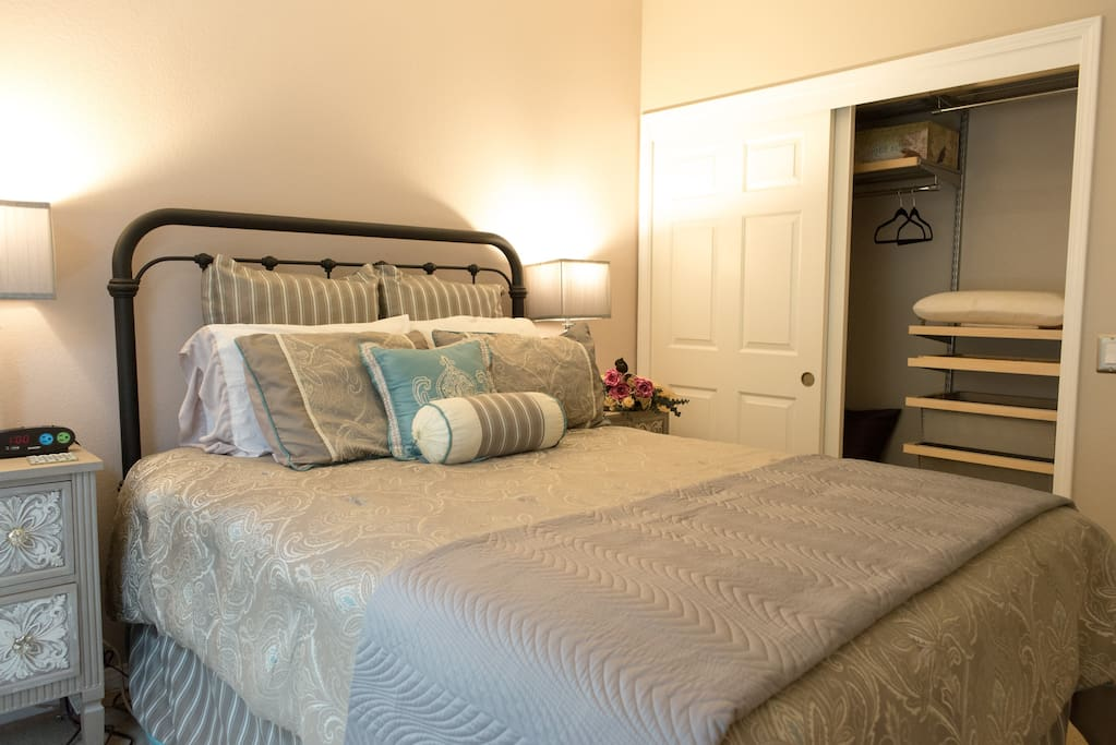 Queen sized bed and closet with shelving and drawers