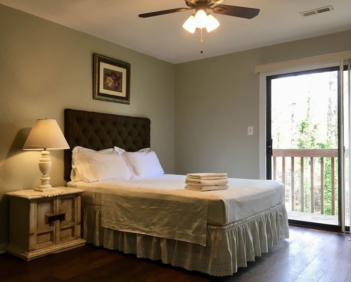 Master bedroom with a queen size bed and balcony