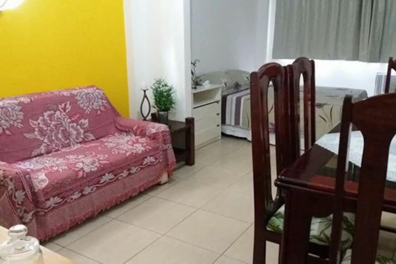 Sala com mesa, geladeira e sofá cama