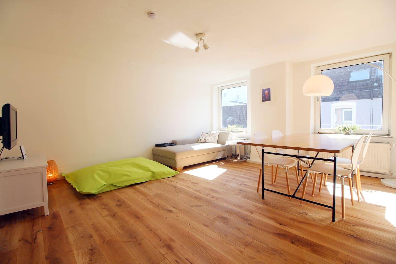 Wonzimmer mit großem Esstisch, Couch, Sitzsack und TV.
