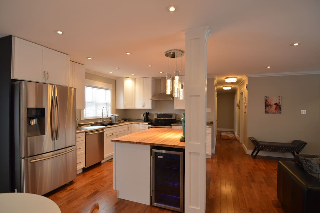 Gourmet kitchen with stainless steel French door fridge, double oven and glass top stove, dishwasher, and a wine fridge!
