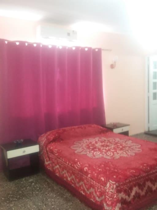 Vista de la cama y la cortina hacia la ventana