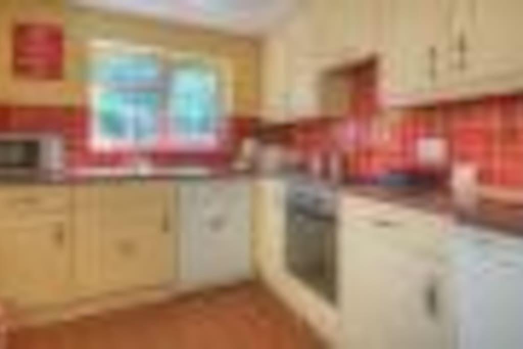 Modern kitchen with oven, hob, microwave, fridge freezer & dishwasher.