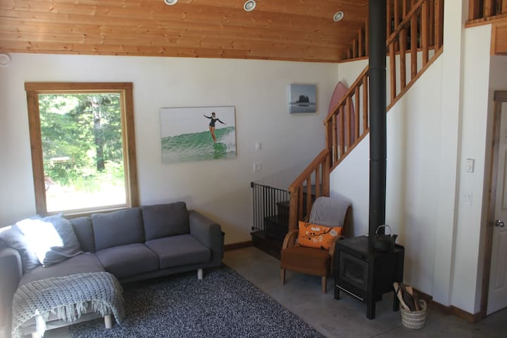 Main floor living space with natural light and large windows looking into the woods. Woodstove available for heat and coziness!