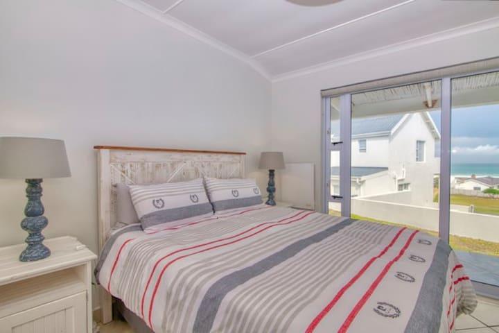 Main bedroom with sea view . Queen Bed. En suite bathroom with shower.