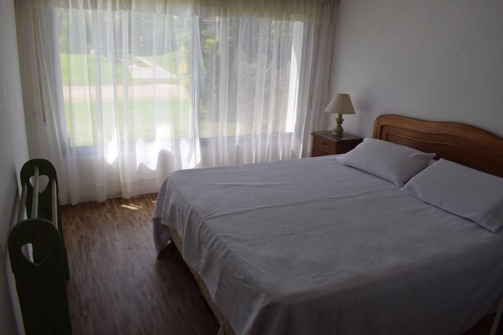 Dormitorio matrimonial con cama Queen size, en suite, vista frente.