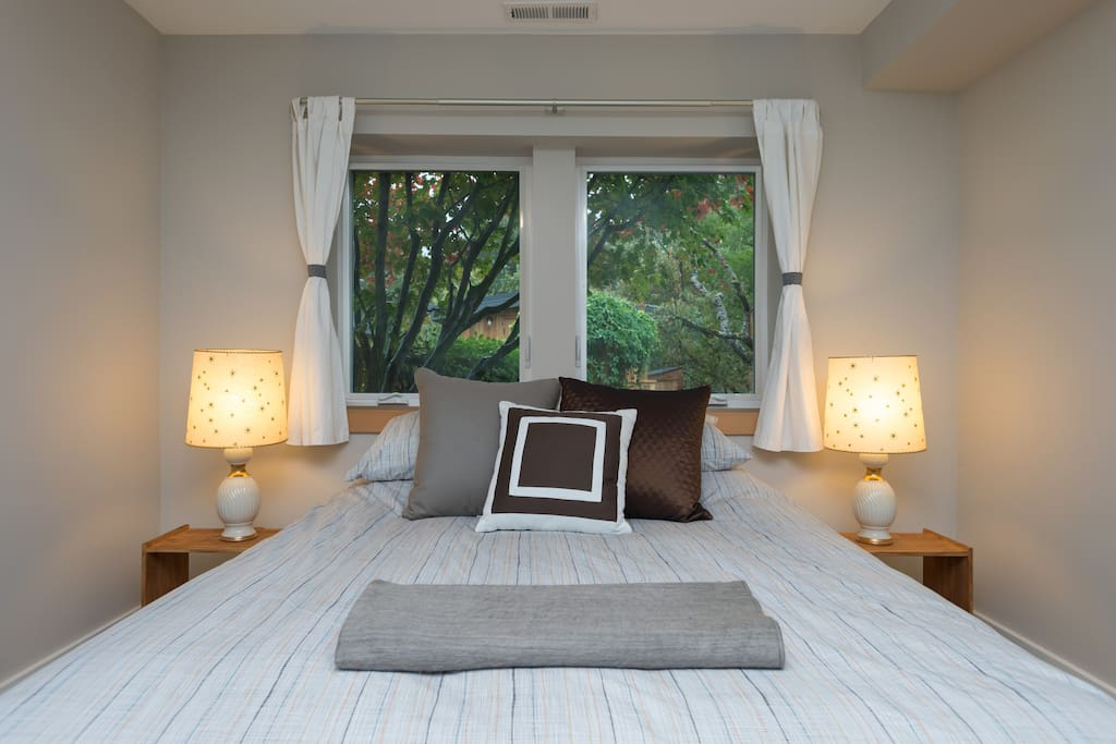 Bedroom with queen-size bed and garden view.