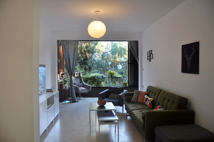 Cozy and colourful lounge entertainment room, with big windows to a everlasting green Grove