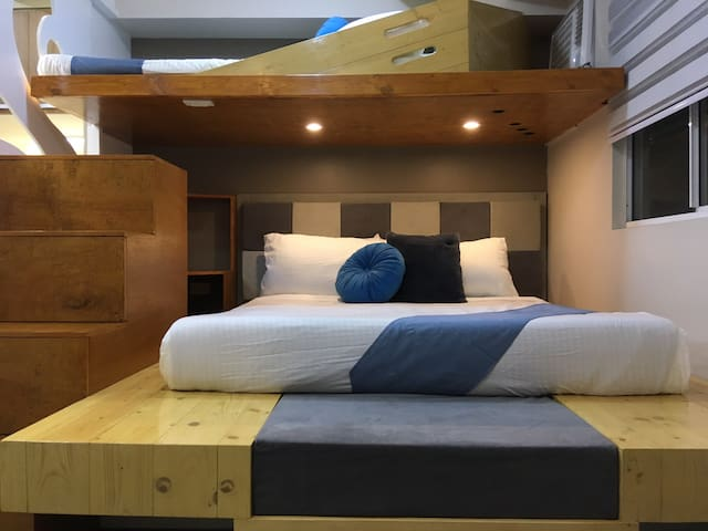 """A queen bed with standard hotel matress set in a japanese inspired """"tatami"""". A loft for another guest is seen above for a comfy tuck. A computer nook is seen aside."""