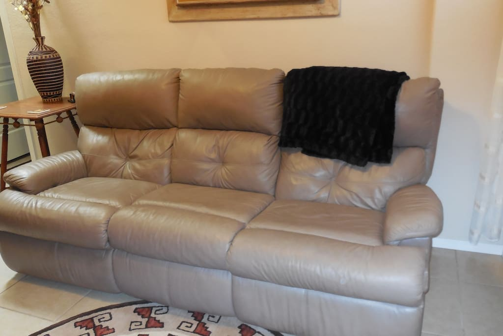 The comfy leather sofa (70 inches long) can accommodate  1 adult for sleeping if necessary.