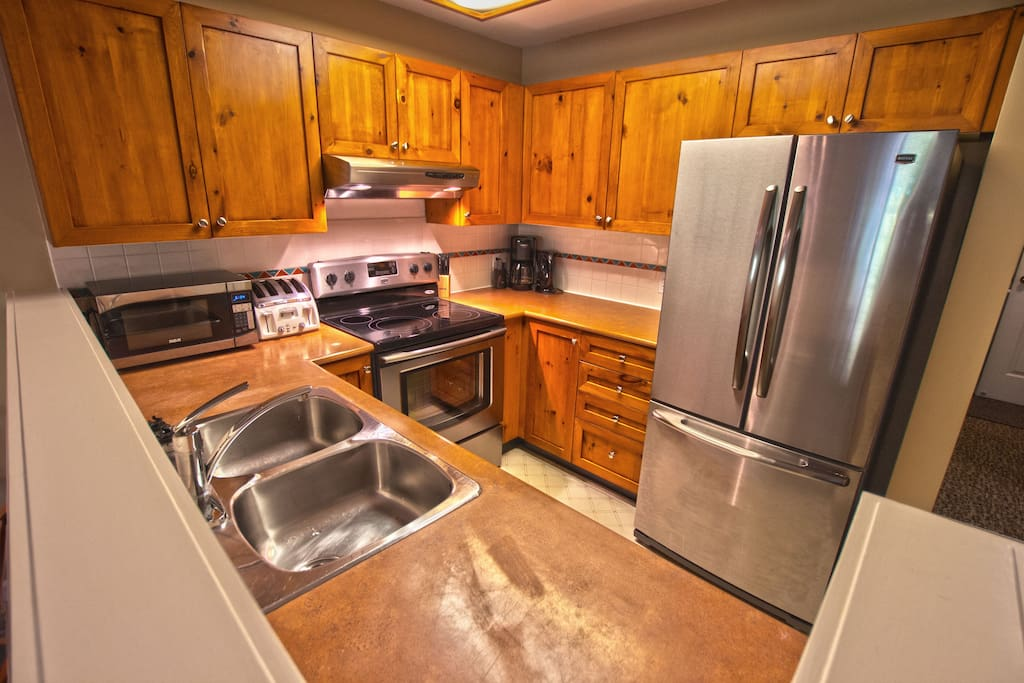 Kitchen - Fully equipped with new Maytag appliances, cooking utensils, and glassware for gourmet home cooking.