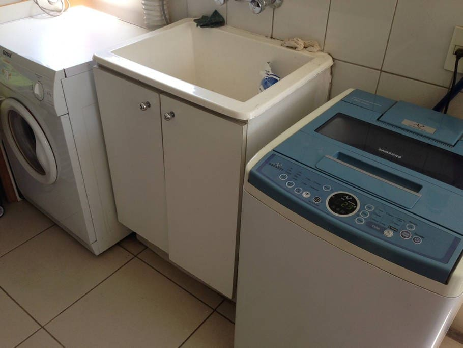 Laundry room with washer and drier available for use.