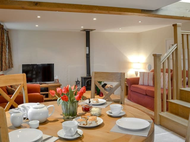 """⭐️ The Cottage lounge and dining area with a log burner and smart TV. Katrina, from Banbury: """"We really enjoyed the cottage and had a few fires on the log burner, which was really cosy after long days on the beach with our 4 & 8 year olds!!"""""""