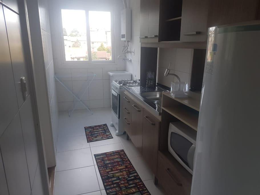 Cozinha equipada com fogão, microondas, cafeteira, louças, geladeira, água quente e churrasqueira.