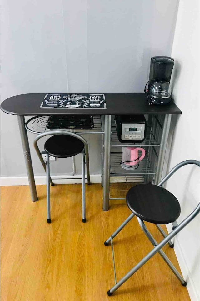 Can be a work space or dining space with coffee maker, water heater, rice cooker, place mat, dish tray and two chairs