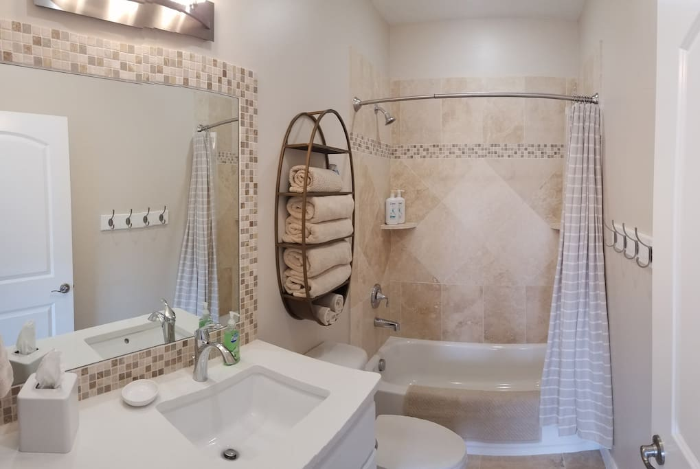 Classic Bathroom with expert detail in travertine stone tile work. Large quartz counter tops and endless hot water heater.