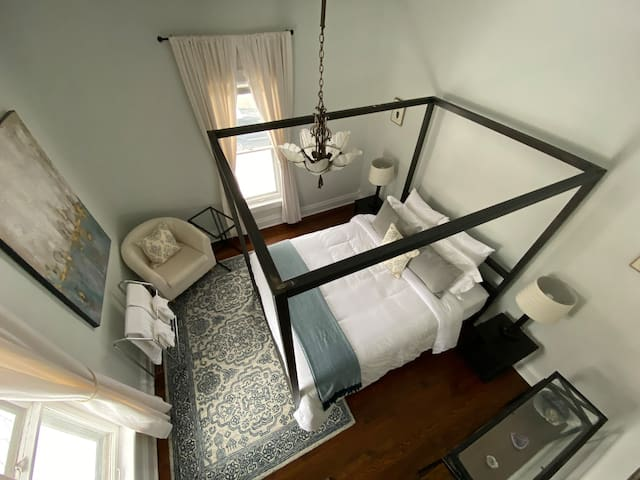 Sleep like a Queen in this lovely bedroom with Northwest views. A beautiful antique chandelier dips beneath the canopy. The Bedside lamps have power outlets to charge all your devices. You will find a luggage rack in the closet for your convenience.