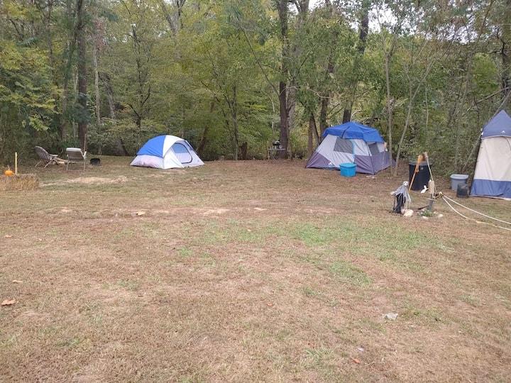 Creek bank/tent/shower/power/water/heat/bedding