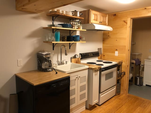 Kitchen with microwave, fridge, stove, toaster oven, dishes, spices, pots and pans, coffee and tea pot