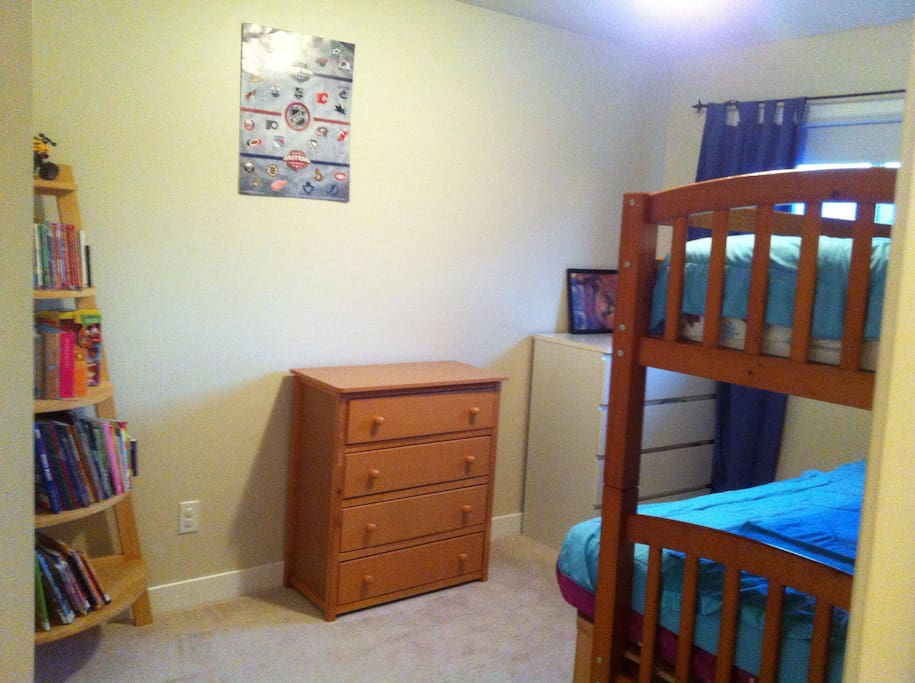2nd bedroom with single over double bunk. Two dressers and fully stocked kids bookshelf
