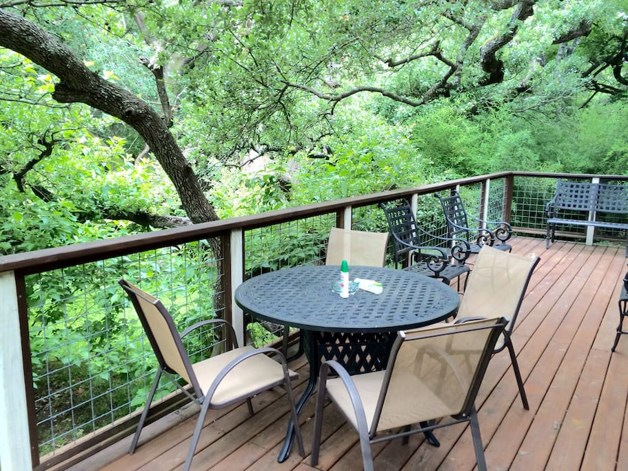 The canopied tree covers back porch that is connected to the den/kitchen /dining common area . Enjoy this peaceful environment while the kids play in the huge lush lawn amongst the trees and flowers .