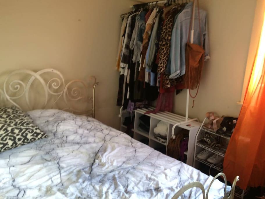 Double bed, clothes rack, cube storage space and shoe rack. Window to the backyard.