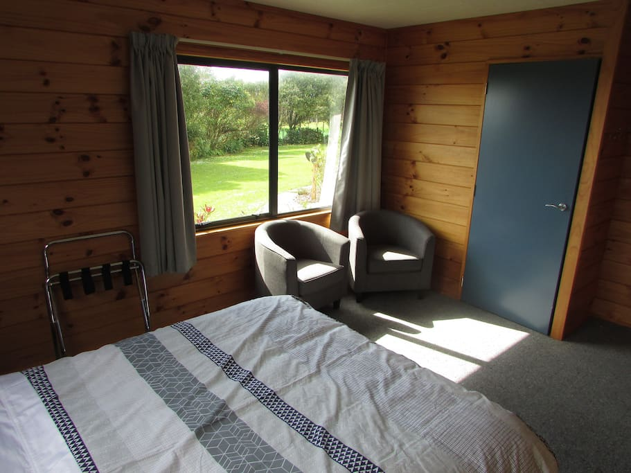 ueen bed with view of garden and sea over the trees. Sunny room