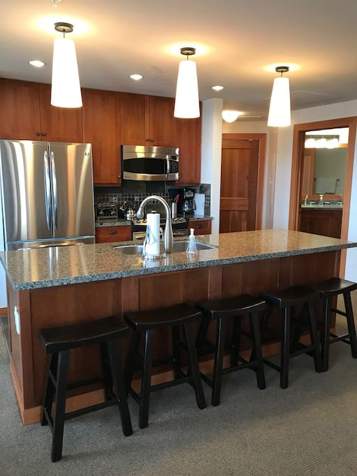 Fully Equipped Gourmet kitchen with large island and bar chairs.  Stainless steel appliances and granite counter tops.