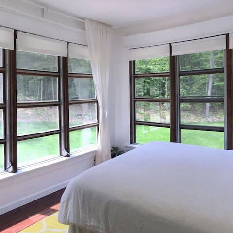 Two solid walls of windows provide breathtaking views of the forest and rolling lawns.