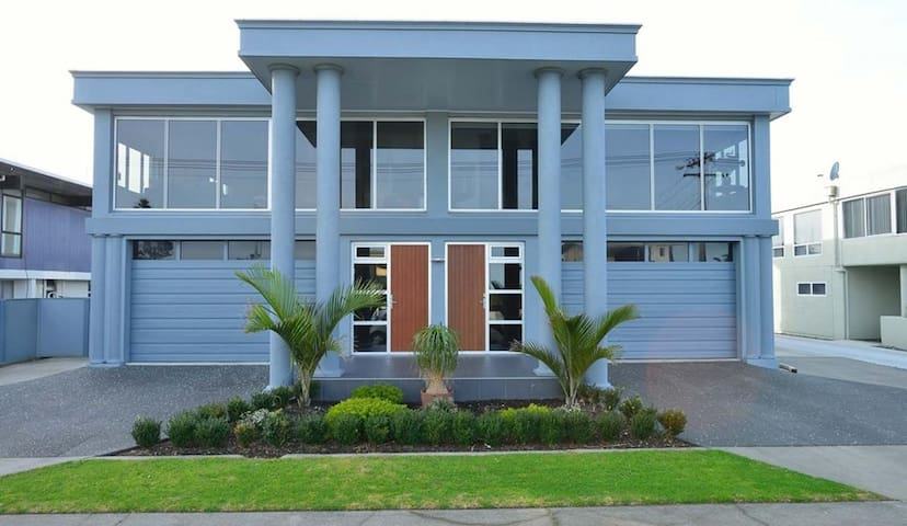 The apartment extends from behind the left garage door. Behind the garage door is a carpeted and spacious sitting area & fully equipped kitchen & extra beds (king single, trundler). Behind that, a further living area leading to bedrooms and pool deck