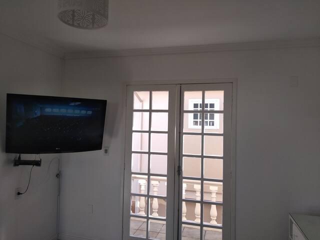 Visão da entrada do imóvel. Sala com TV de Led.