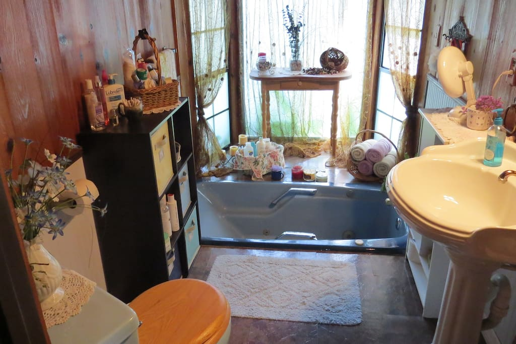 First bathroom has a sunken jacuzzi tub with a bay window. Blow dryer and toiletries on hand.
