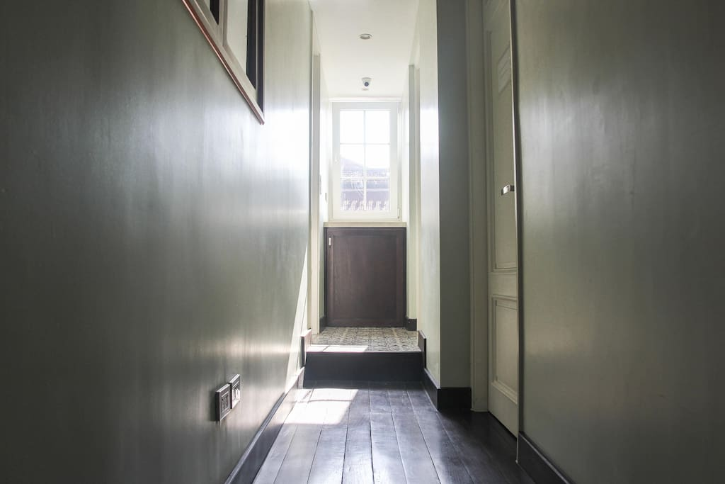 Sunshine filled hallway. In that little cabinet is a washing machine, and yes, it is free for you to use.